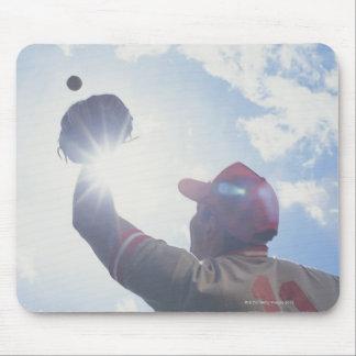 Bola de cogida del jugador de béisbol con el sol e tapetes de ratón