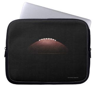 Bola del fútbol americano en fondo negro mangas computadora