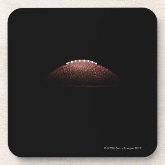 Bola del fútbol americano en fondo negro posavasos