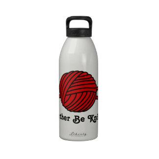 Bola roja del hilado y de las agujas que hacen pun botella de agua