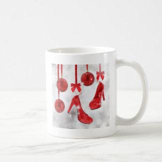 Bolas rojas de los tacones altos y del navidad y taza de café