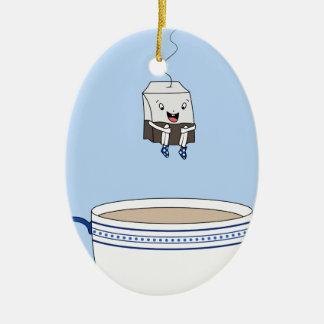 Bolsita de té que salta en taza adorno navideño ovalado de cerámica