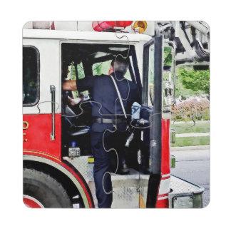Bombero que sube en el coche de bomberos posavasos de puzzle