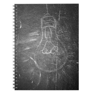 Bombilla en una pizarra spiral notebook