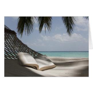 Book on a hammock under a palm card