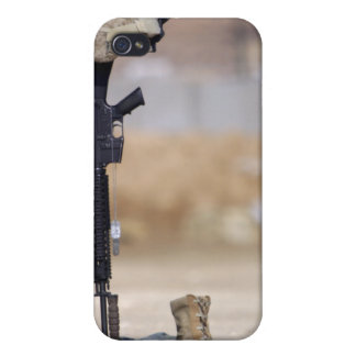 Boots, rifle, dog tags, and protective helmet iPhone 4 cover