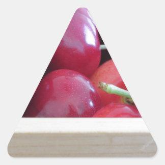 Border of fresh cherries on wooden background triangle sticker