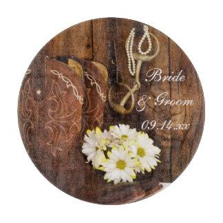 Botas de vaquero, margaritas y boda del pedazo del tablas para cortar