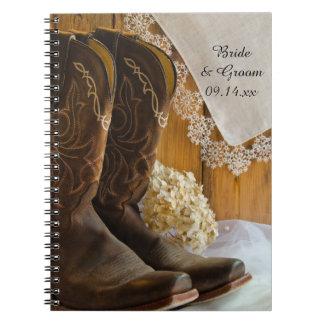 Botas de vaquero y cuaderno del boda del país del