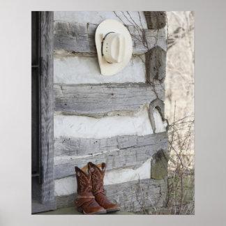 Botas y gorra de vaquero fuera de la cabaña de póster