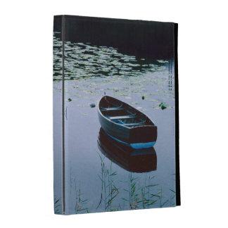 Bote de remos en el pequeño lago rodeado por el ag