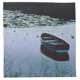 Bote de remos en el pequeño lago rodeado por el ag servilleta imprimida