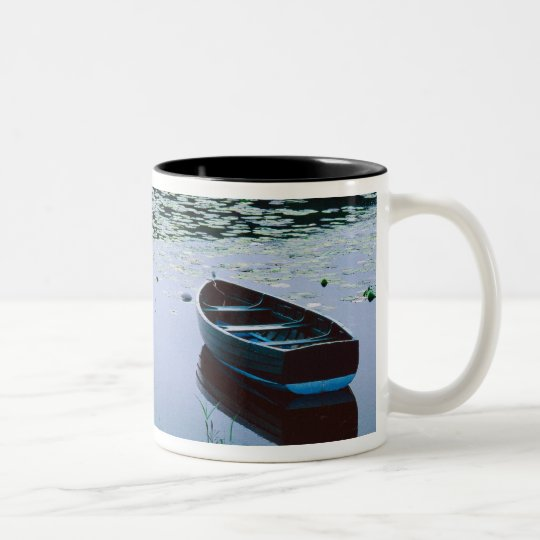 Bote de remos en el pequeño lago rodeado por el taza de café de dos colores