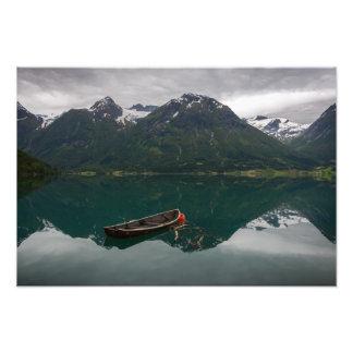 Bote de remos viejo con la reflexión de la montaña cojinete