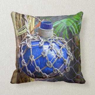 botella de cristal azul en red contra la cerca almohada