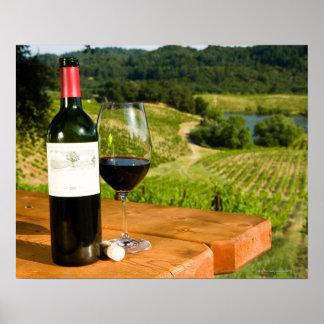 Botella de vino rojo y de vidrio en la tabla poster