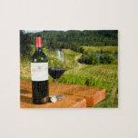 Botella de vino rojo y de vidrio en la tabla puzzles con fotos