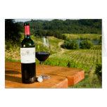 Botella de vino rojo y de vidrio en la tabla tarjeta