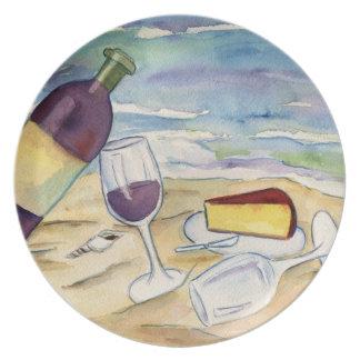 Botella y vidrios de vino en la playa platos de comidas