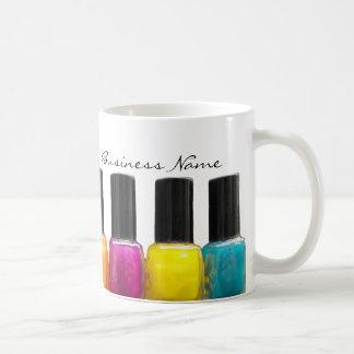 Botellas coloridas del esmalte de uñas, salón del taza de café