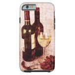 Botellas con el vino, la copa de vino blanca y las funda de iPhone 6 tough
