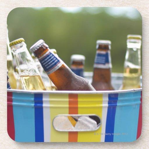 Botellas de cerveza en cubo de hielo posavasos