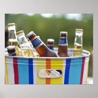 Botellas de cerveza en cubo de hielo póster