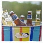 Botellas de cerveza en cubo de hielo teja