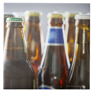 Botellas de diversa cerveza en botella en estudio azulejo cuadrado grande