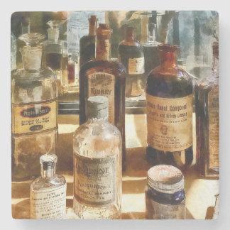 Botellas de la medicina en el caso de cristal posavasos de piedra