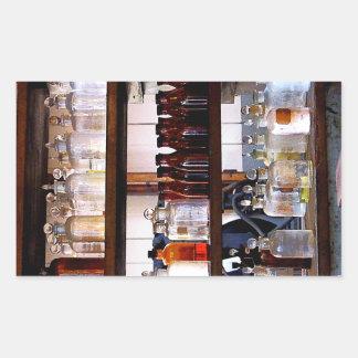 Botellas de sustancias químicas en estantes pegatina rectangular