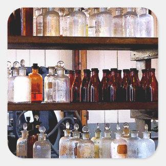 Botellas de sustancias químicas en estantes pegatina cuadrada