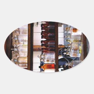 Botellas de sustancias químicas en estantes pegatina ovalada