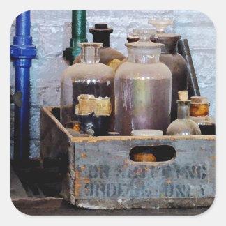 Botellas de sustancias químicas en una caja de pegatina cuadrada