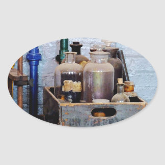 Botellas de sustancias químicas en una caja de pegatina ovalada