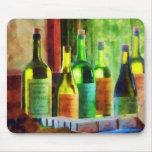 Botellas de vino cerca de la ventana alfombrillas de ratón