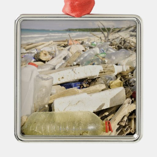 Botellas plásticas y océano que descargan en un adorno navideño cuadrado de metal