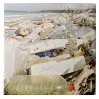 Botellas plásticas y océano que descargan en un azulejo cuadrado grande