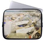 Botellas plásticas y océano que descargan en un mangas portátiles