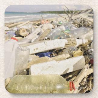 Botellas plásticas y océano que descargan en un tr posavasos de bebidas