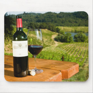 Bottle of red wine and glass on table mouse pad
