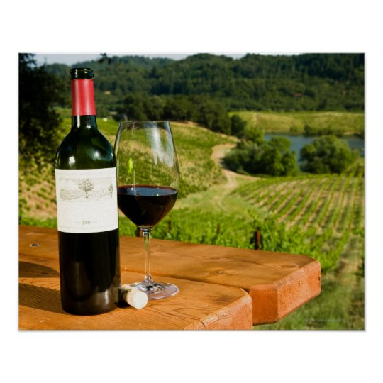 Bottle of red wine and glass on table poster
