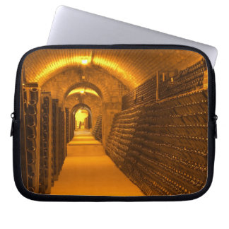 Bottles aging either in pupitres (racks) waiting laptop sleeves
