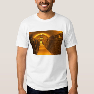 Bottles aging either in pupitres (racks) waiting tee shirt