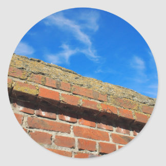 Bottom view on a fragment of red brick fence classic round sticker