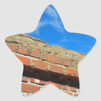 Bottom view on a fragment of red brick fence star sticker