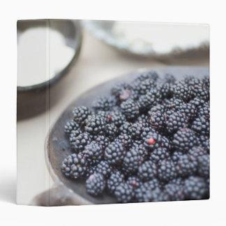 Bowl of blackberries on a table 3 ring binder