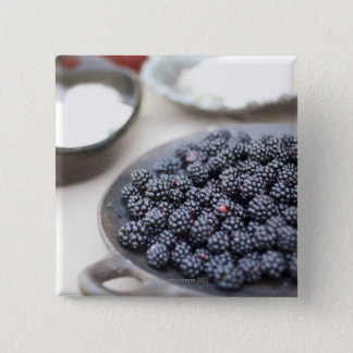 Bowl of blackberries on a table button