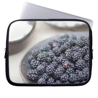 Bowl of blackberries on a table laptop sleeve