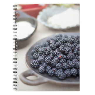 Bowl of blackberries on a table spiral notebooks